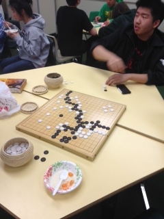 Students play Go.  Go is played with a wooden grid board, and many many white and black stones.  The teams are black versus white.  The game can last several hours, and despite it's simple appearance, it is quite complex.