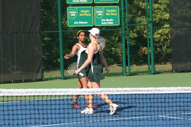 After winning a point, teammates senior Sneha Rajagopal and junior Brianna Dooley celebrate with a high five. This is a common act after a victory that is encouraged by the coaches so players learn to appreciate their partners.