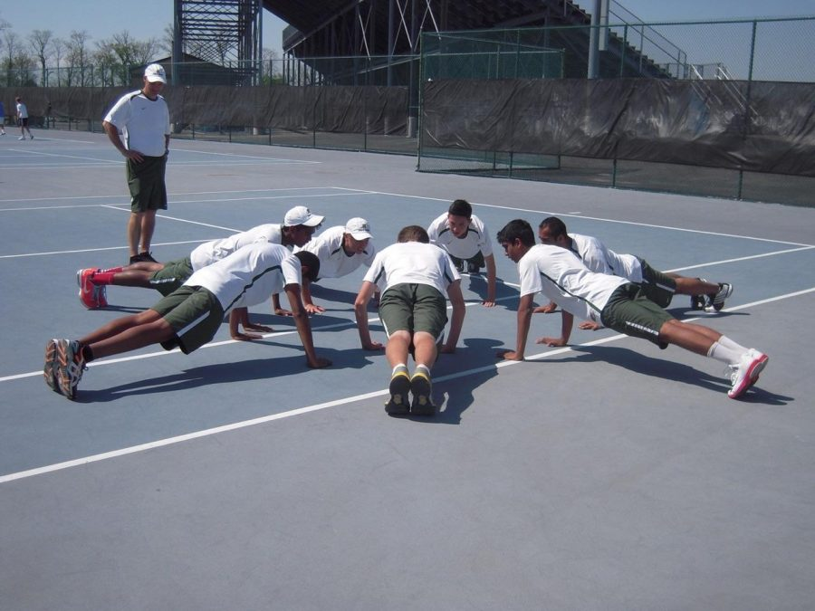The+Varsity+tennis+team+took+home+the+school%E2%80%99s+first+State+title+in+the+2014+season.+Before+each+match%2C+they+partake+in+warm+up+drills+such+as+pushups+to+help+improve+physical+stamina.+They+open+their+season+in+April