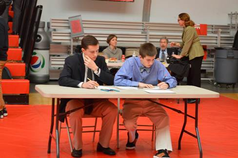 Riley Reddy and Elliot Levy prepare their role play at the district DECA competition . They were participating in the hospitality services team event. The boys placed within the top four teams in the event so they will be going to the state competition in March.