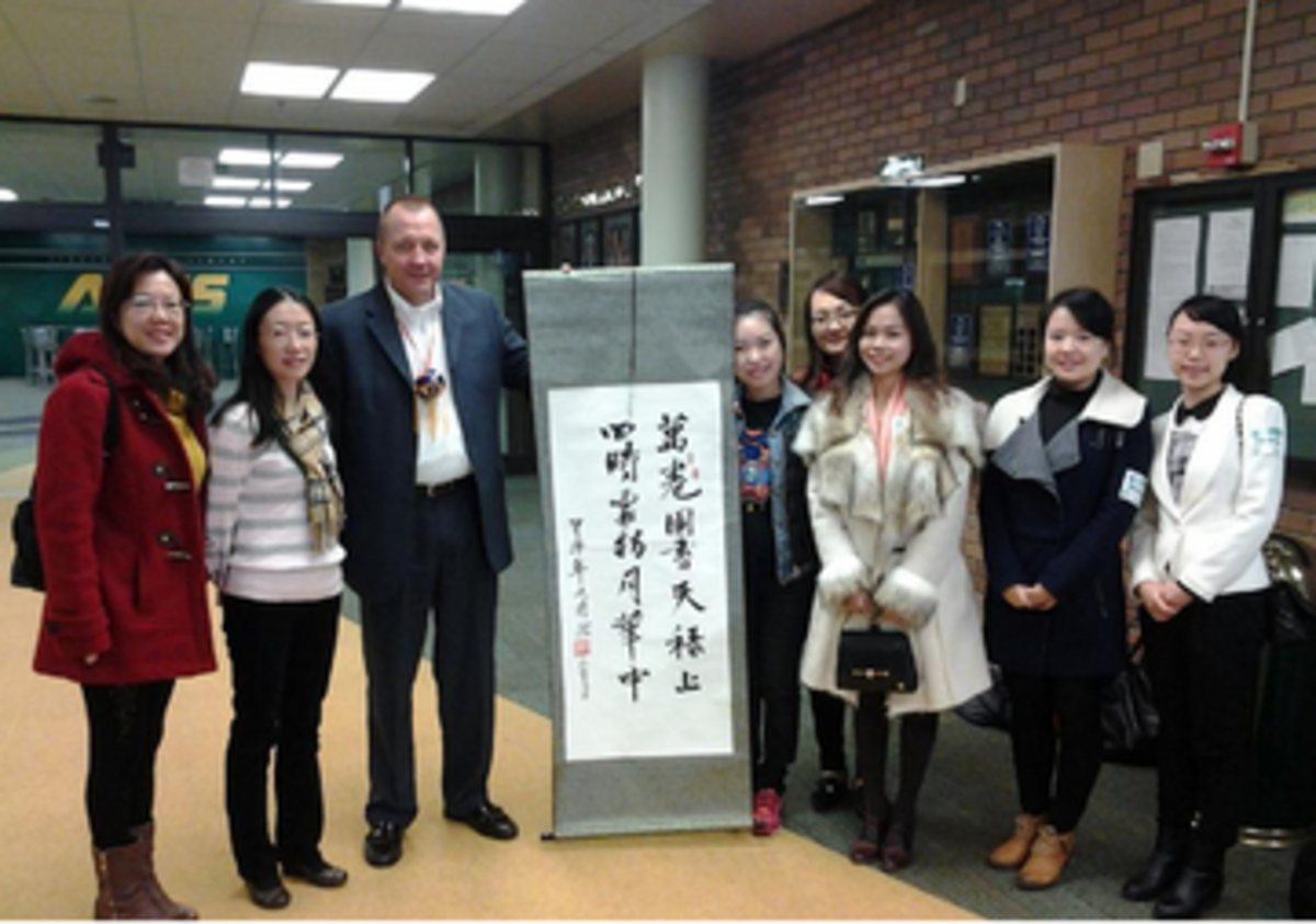 Principal Doug Mader greets several Chinese educators at the front office. The teachers traveled to the United States for five months to learn about the American school system and improve their English. At SHS, they visited several classrooms throughout the day.