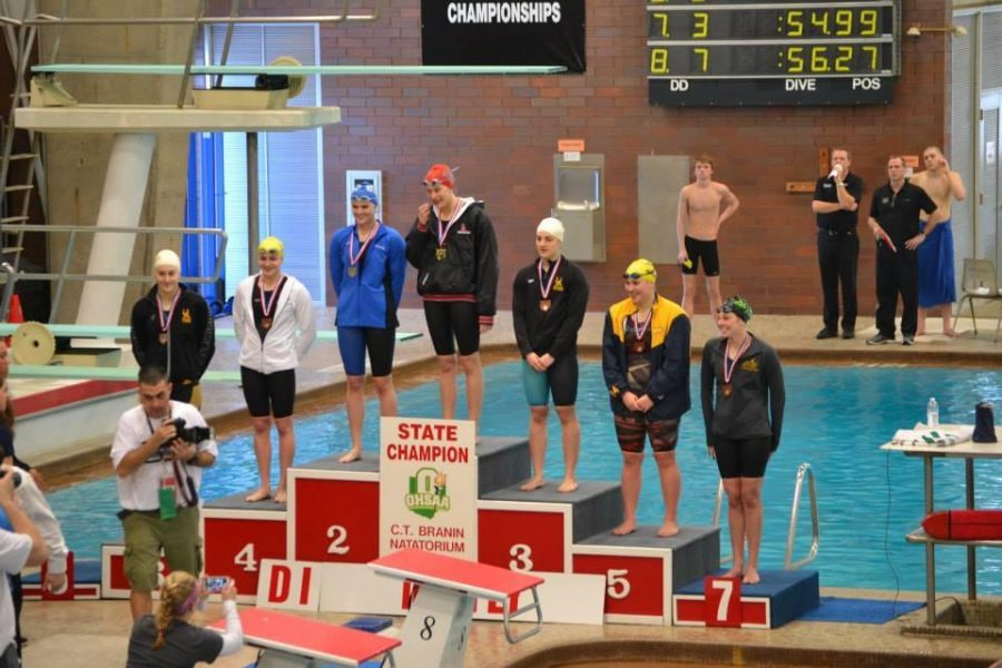 Norris stands on the podium after receiving her medal for her seventh place finish in the 100 fly with a time  of :56.27. Norris injured her knee in the middle of the season, due to this she was  not able to train for a month before the state meet. Last year, Norris got second place in the 100 fly with a time of :55.14, just two one hundredths of a second off of the first place winners time. Photo by Jean Wu.