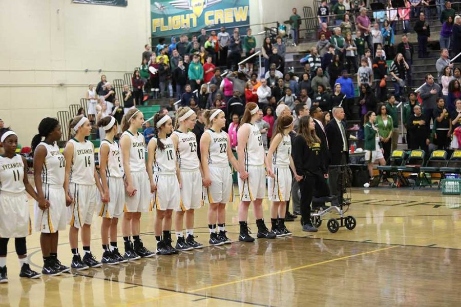 The+girls+varsity+basketball+team+stands+hand-in-hand+during+the+National+Anthem+of+their+last+home+game+against+Princeton.+Their+season+came+to+a+close+after+a+loss+to+Winton+Woods+in+the+first+round+of+the+tournament.+Photo+Courtesy+of+McDaniels+Photography.+