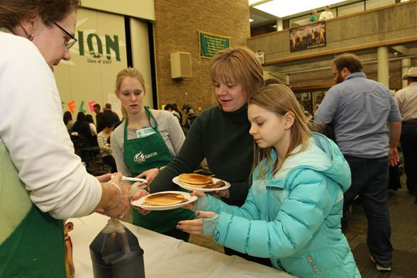 Patrons prepare to enjoy pancakes at the 2014 Pancake Day. Last year more than 2,200 people were fed with over 170 gallons of pancake batter and 26 gallons of syrup. A $6 includes pancakes, sausage, and a beverage as well as seconds. Photo courtesy of McDaniels Photography.