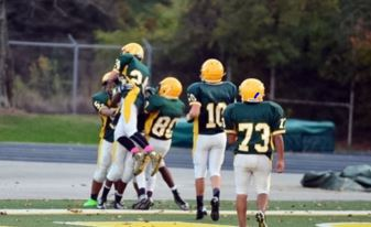 Pictured is: 10 Jackson Rudd, 24 Caedmon Ferrell, 80 Jacob Vayo-Smith, farthest left: Ryan Draughn. The team celebrates after scoring a touchdown. Football is an incredibly dangerous sport and has many risks, which these players know all too well. However, they continue to play despite these risks.