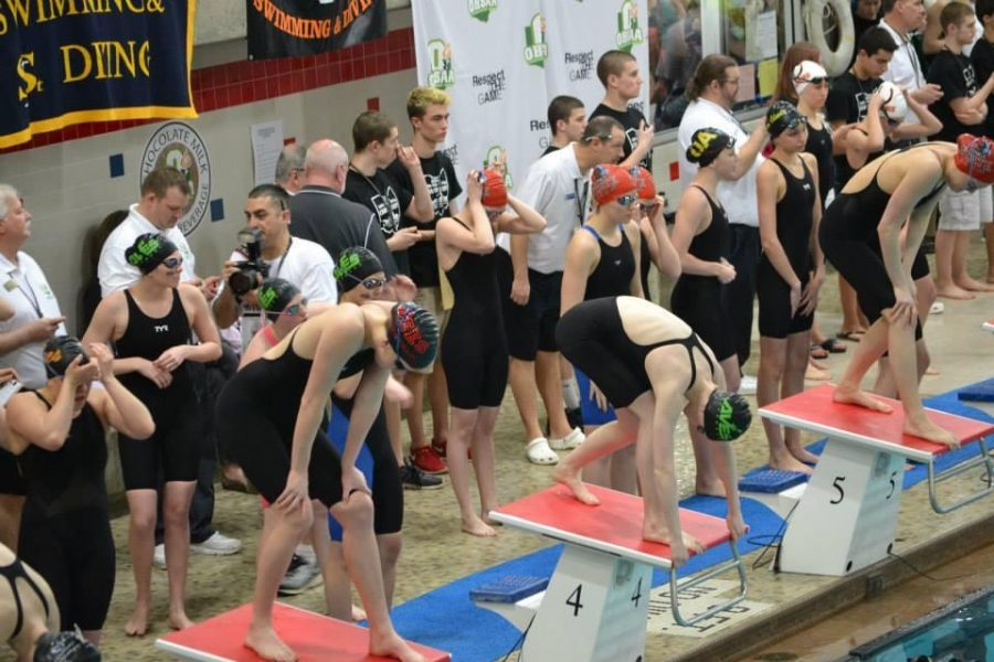 Senior Mary Fry readies herself to swim the lead-off leg of the 200 freestyle relay at the OHSAA State Championship meet. Fry swims for the Mason Manta Rays, a local club team. However, she plans to practice with the high school team this season. Photo by Jean Wu.