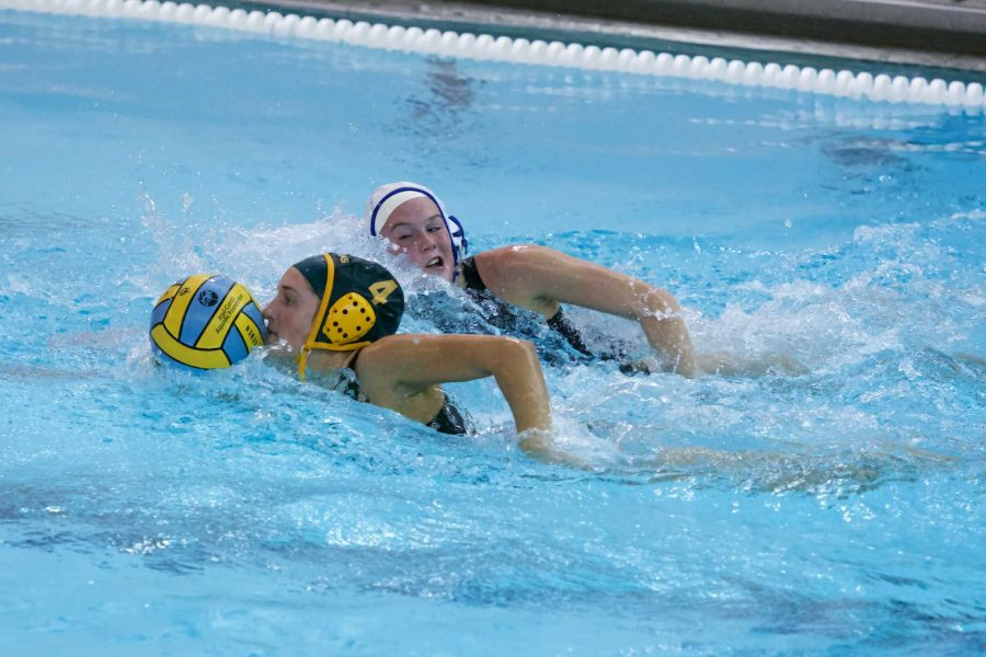 Paige Parr swims the ball down the pool. Parr began playing waterpolo her junior year. She played on Varsity last year and is a starter on the Varsity team this year. Photo by Dale Horne.