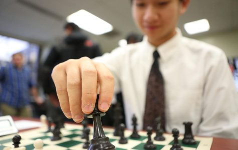 "Sophomore Victor Lim picks up pawn piece in the position F-4 during his turn. Lim played second board throughout the season. Lim was selected as ""first team"" during the GMC competition, meaning he was voted within top ten players."