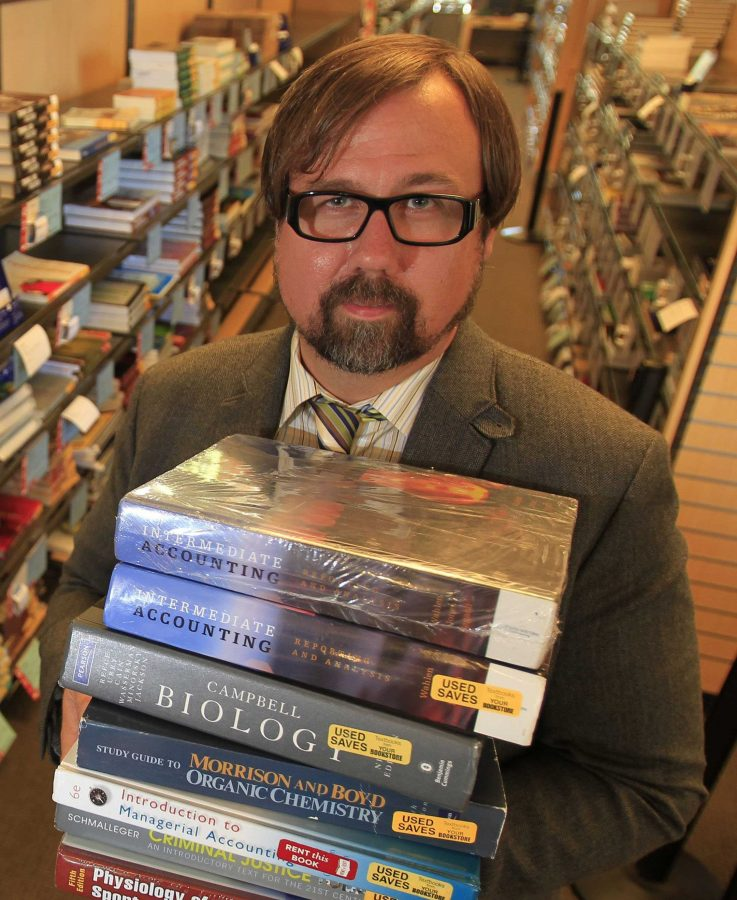 Bookstore manager Brian Lacey holds textbooks that students can rent, buy used, buy new or buy the digital version of at the Cal State Dominguez Hills bookstore in Carson, Calif., which is trying to provide more info to students about book costs and alternatives. (Allen J. Schaben/Los Angeles Times/MCT)