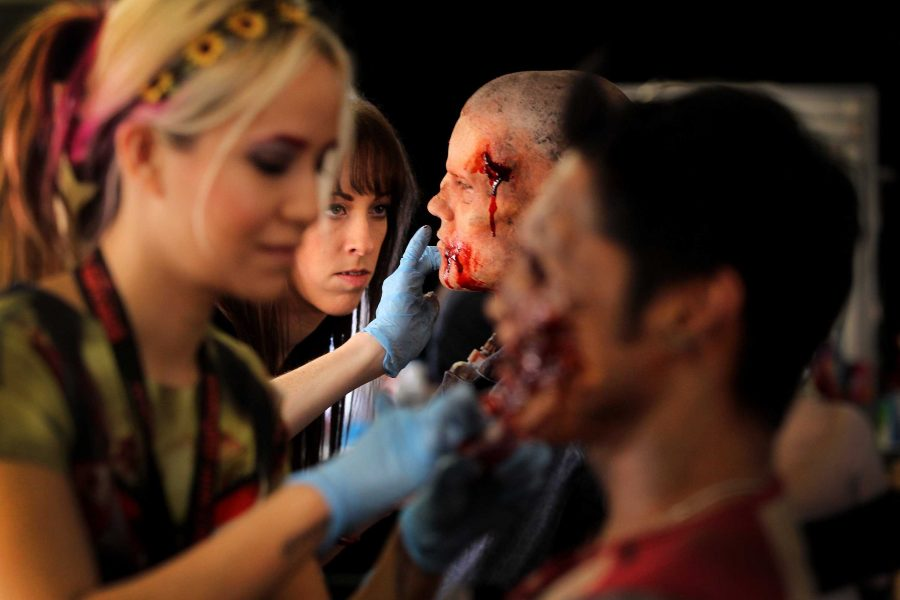 Makeup artists prepare actors for a haunted house. The appeal of haunted houses may be the jump scares and shock value, but horror films need more than that to exceed. Story elements, structure, and cinematography are just as, if not more important.