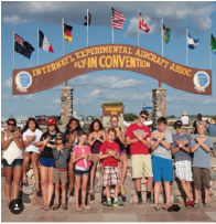 A group of children from the Bonanza group gather in front of the EAA sign , on the Air show grounds. They have all been coming here for multiple years, most of them, including Evans, since they were just a year old. They take a photo in front of this sign every year to commemorate the adventures they have in Oshkosh. In this photo, taken in 2015, sophomore Sydney Evans and junior Lauryn Kylop, Grace Matther, and Sarita Evans are all standing on the right.