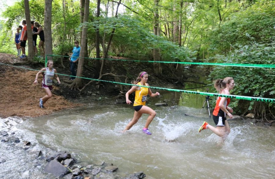 Sophomore Olivia Anapole as she crosses the first of two creeks. The creeks were about shin deep, and many girls fell in this body of water. After getting up the small hill afterwards, runners must go up the infamous mulch hill.
