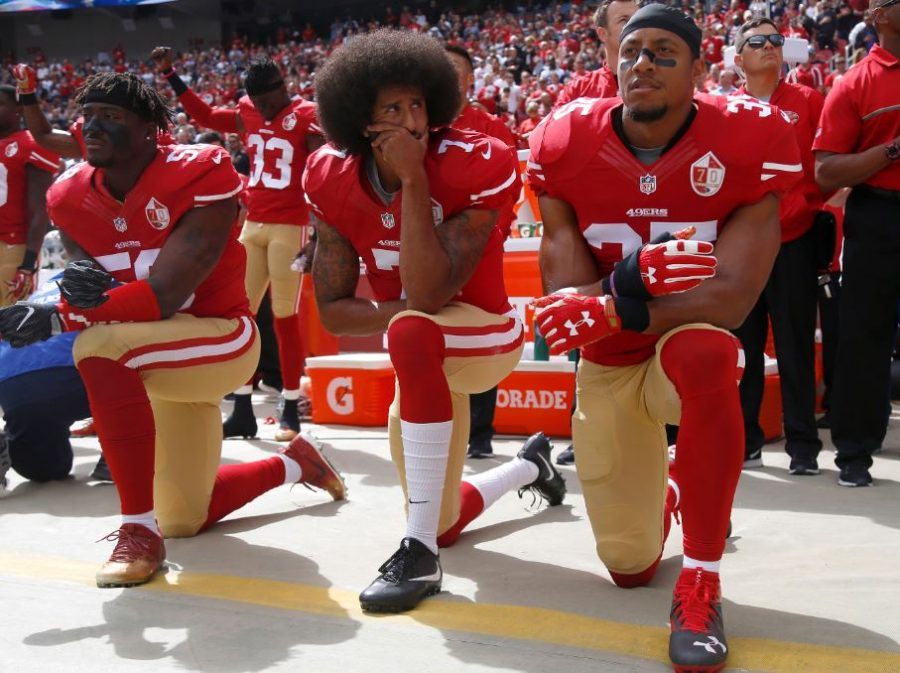 San Francisco 49ers' Eli Harold, Colin Kaepernick, and Eric Reid kneel during the national anthem before their NFL game against the Dallas Cowboys on Sun. Oct. 2. This form of protest has spread among professional and high school athletes as part of the Black Lives Matter movement. These acts have been criticized for disrespecting the anthem.