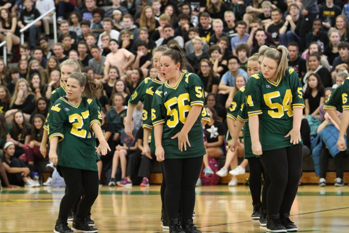 """HITTING IT. The Flyerettes are performing their routine. For the team, the pep rally symbolizes the beginning of their performance season; while they are aiming for more fall events to dance at, this is normally their first big performance. For the two four year seniors, it was an emotional time that marks the beginning of the end to their high school dance career. """"The Homecoming pep rally was really exciting because it was our chance to show the school what we are made of. I loved performing that dance and it made my last pep rally something to remember,"""" said Hannah Young, 12 and co-captain."""