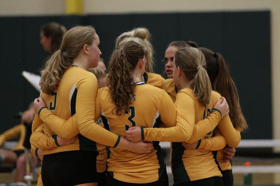 TEAM TIME. The girls freshman volleyball team huddle together before their game against on September 13th. They support each other with cheers and hugs.