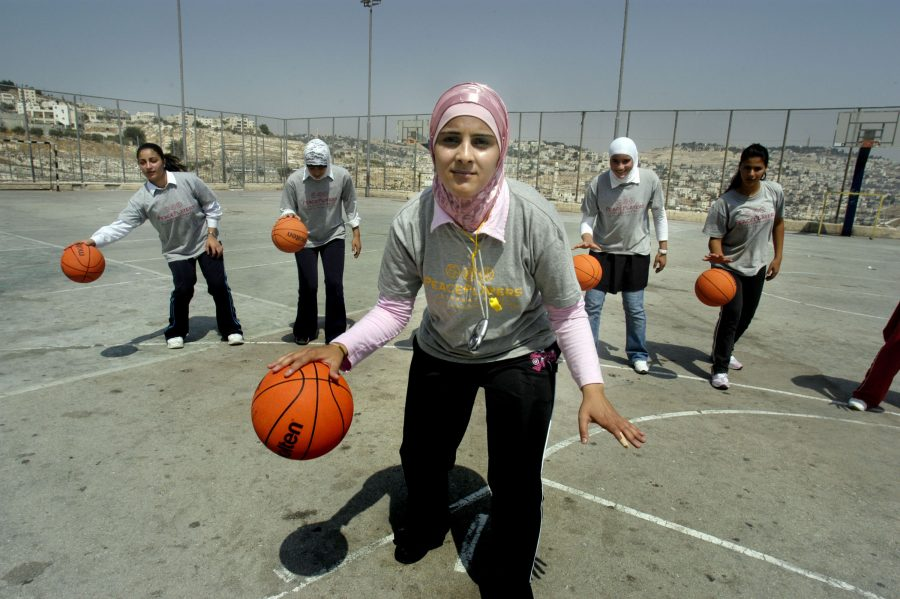 SCORE. Young girls play basketball in hijabs, the traditional Muslim head dress. The International Basketball Federation is planning to lift its regulations concerning religious headgear. The attire, including hijabs and yarmulkes, has been banned due to safety reasons, but cries for equal opportunity for people of all sexes and faiths have sparked changes.