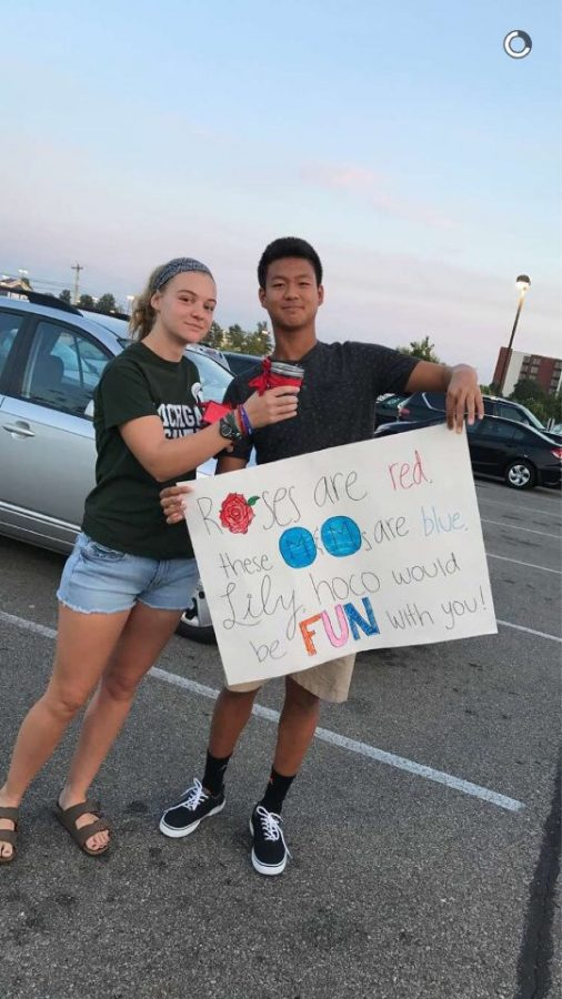 """SWEET SURPRISE. Nathan Zhang, 12, asks Lily Martinson, 12, to Homecoming using a poster and candy. """"Homecoming is always a fun night. Getting to dance and hang out with your friends is an experience you can't miss during high school. [Lily] thinks blue M&Ms taste better than the other colors,"""" Zhang said. Many students use posters to ask their dates to prom with a silly saying, a pun, or a joke. All photos courtesy of Staff."""