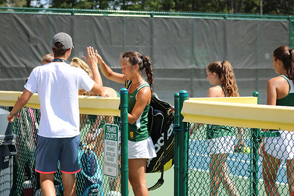 ENCOURAGEMENT. Junior Alex Karev high fives senior Kaitlyn Jiang after a match. High-fives are a trademark of Aves tennis as a way to maintain positive energy on the court.