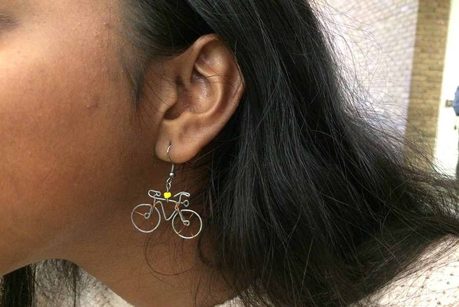 """CONNECT. Sophomore Shruthi Chidambaram displays her wire-and-bead bicycle-shaped earrings. The earrings were made by Afrika Pamoja, a fair trade project in Kenya where young women can earn a living by learning to make handicrafts. """"They're really fun and unique, and it feels really good knowing that you're helping underprivileged people,"""" Chidambaram said. All photos courtesy of Anisa Khatana."""
