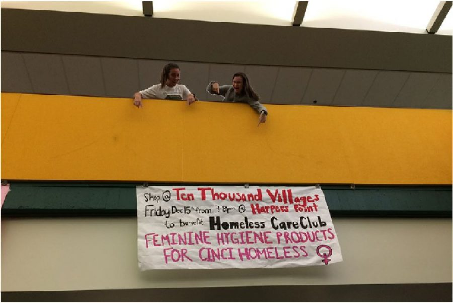 """LOOK! Junior Peyton Gilhart and senior Jodie Lawson gesture to the promotional banner that HCC has hung in the Commons. Club members came together after school to design and paint the banner. Students– or anyone interested– can come to TTV's Harper's Point Location from 3:00 p.m. to 8:00 p.m. for the """"Sip and Shop"""" event advertised here. """"Students should participate in this fundraiser because of the benefits it brings to homeless women in Cincinnati and the global benefits of Ten Thousand Villages,"""" said HCC general officer Tabitha Cady, 11."""