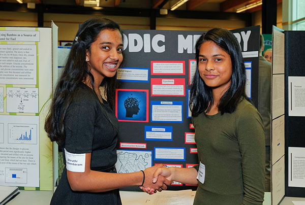 "CHANGING THE GAME. Sophomores Debasmita Kanungo and Shruthi Chidambaram are pictured at the science fair last year, presenting their research on how different instrumental music affected memory in the classroom environment. ""The most important part of the experiment is that it has some type of a social impact and improve society in one way or another, "" Kanungo said."