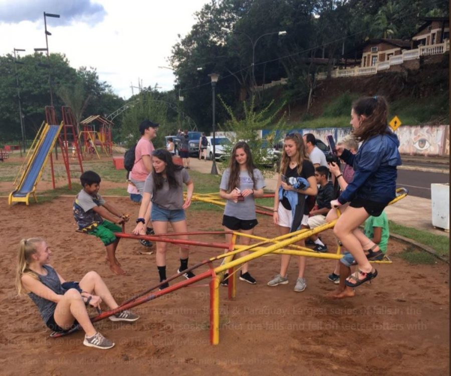 FUN. Students on the Argentina field trip with Ms. Blackmore fall off the teeter totters with local children. They also visited the Cataratas de Iguazú, which is the largest series of falls in the world, located between Argentina, Brazil, and Paraguay. So far, the students have tweeted images of them hiking, getting soaked under the falls, and learning to tango.