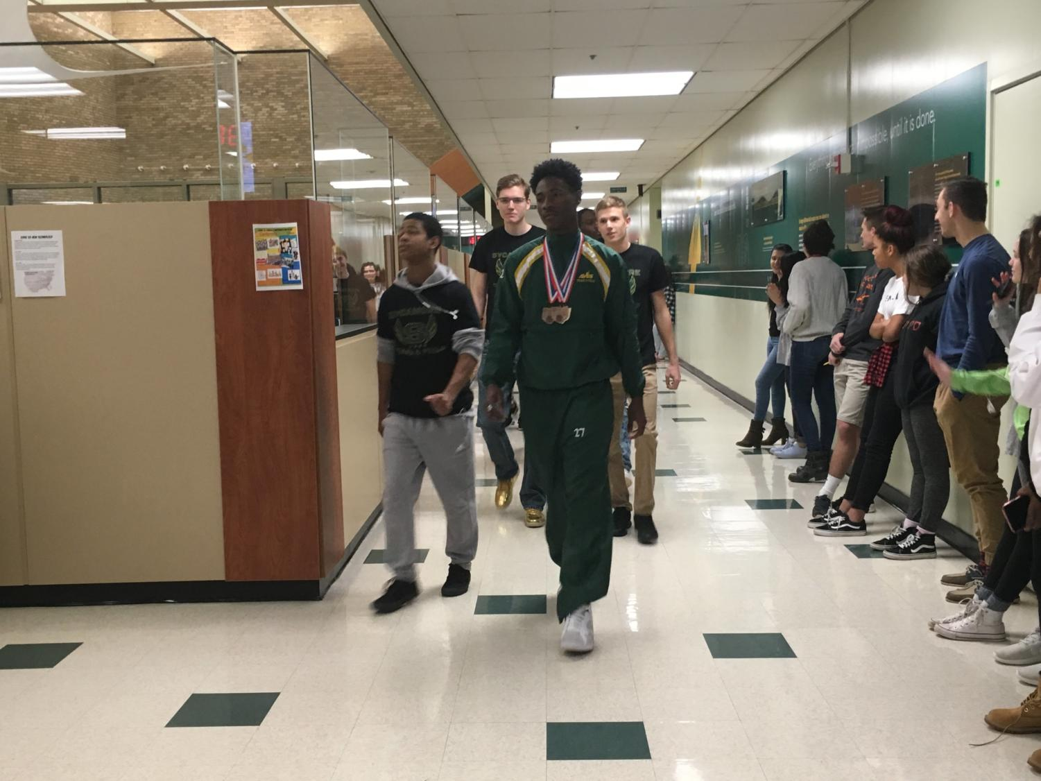 SPIRIT. A walk of champions celebrates the winter track athletes before they head to state. Senior Asa Hodrick ranked seventh in the 200m. Athletes had to rank in the top eight at the event to earn points for their team as a whole.