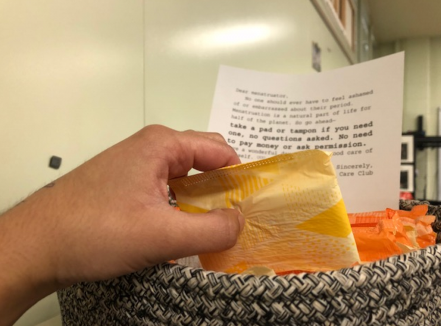 """GO AHEAD, TAKE ONE. A student takes a pad from HCC's basket of free menstrual products. Room 152 is located in the downstairs art/language hallway at the end of the hall nearest to the exit doors, and sits directly across from a set of restrooms. Upon entering Room 152, look to the left to find the black and white woven basket sitting atop a stack of filing cabinets. """"I'm excited to see [what] HCC… will do next to help improve SHS,"""" said Connor Close, 11."""