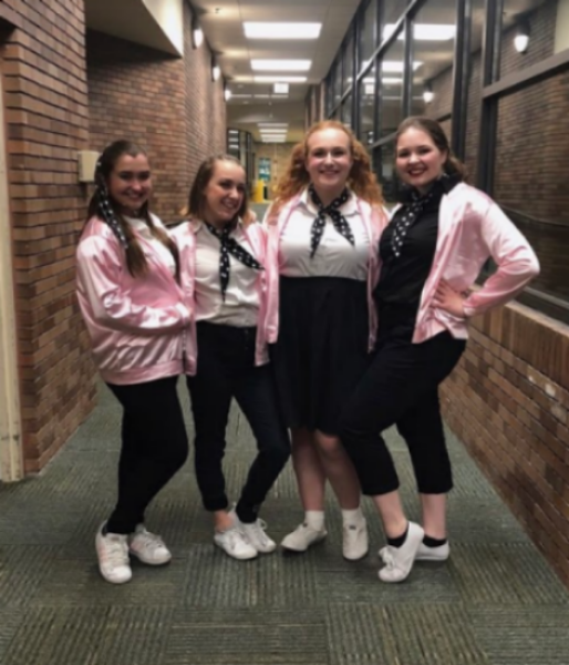 "LIGHTS, CAMERA, SMILE. Juniors Erin McDonough, Maggie Ballard, Bethany Brown, and sophomore Brynn Gvozdanovic posed for photos during the ""Grease"" rehearsals. They dedicated eight weeks of hard work and time into this musical, building a theatre community and friendships. ""Since this cast is relatively small, we all have grown very close during the process...I just feel like everyone trusts each other a lot, and that's really important for a show, everyone relies on each other for so much,"" McDonough said."