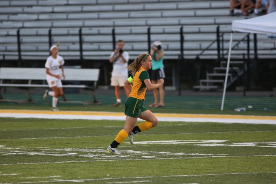 """DARTING. Three year varsity starting midfielder, senior Hannah Kirkham, sprints after the ball in the home match against Walnut Hills. The team went on to defeat Walnut Hills 5-0 and they are currently 7-1-2. """"I think senior night is a great way to recognize the end of a chapter. It's easy to get caught up in the excitement of what's coming next, but it's just as important to look back on on all the things we have accomplished this season and the people that we have accomplished them with. This year especially we've gotten to become a really close knit team so it's definitely going to be a special night,"""" Kirkham said."""