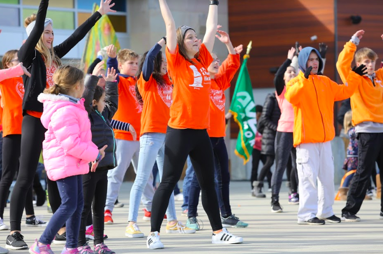 """BE KIND. Participants dance during Cincinnati's Dance for Kindness at Summit Park. The purpose of the dance is to look beyond everyone's differences and spread kindness throughout the world. The participants performed the same dance as all of the other cities and countries around the world. """"Kindness is the common thread that connects us all,"""" said Ms. Joy Nichols, Sycamore preschool teacher and event leader."""
