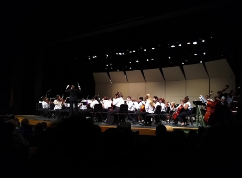 """BOW ON THE STRING. Sycamore Orchestra Director Dr. Angela Santangelo conducts the combined seventh and eighth grade orchestras at the annual orchestra winter concert. After each grade performed separate pieces, they came together to play the final two. """"It was really cool to see [the junior high kids] play pieces as separate orchestras and then combine to play a piece together,"""" said Alice Lundgren, 11, cellist."""