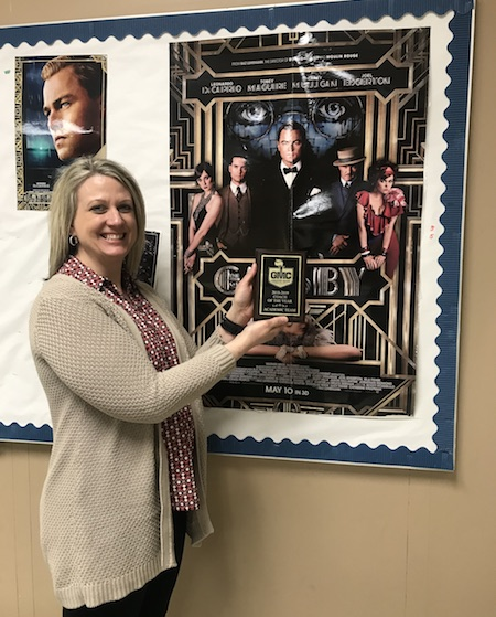 """STRIKE A POSE. English teacher and Varsity AQT coach Mrs. Laura Newton poses with her plaque declaring her the GMC Coach of the Year for AQT.  Newton looks forward to seeing the team compete on April 6 at Regionals. """"It was exciting… I like coaching AQT so I don't really need the accolades but it was fun,"""" Newton said in response to her reaction to winning the spot."""