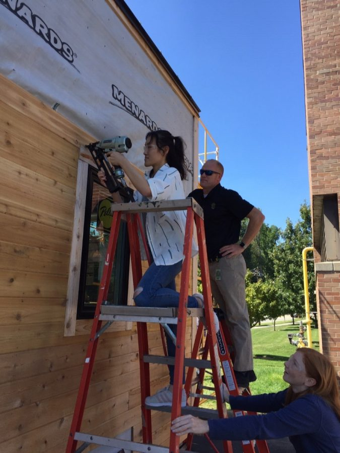Students in Mrs. Callie Hoffman's multivariable calculus class helped build the architecture and engineering classes' tiny house during first quarter. The students benefited from the hands-on application of what they were learning in math to the project. Pictured are seniors Ariane Clerc and Angela Peng nailing siding to the house, and seniors Kevin Mercurio and James Hanus cutting a wooden plank.