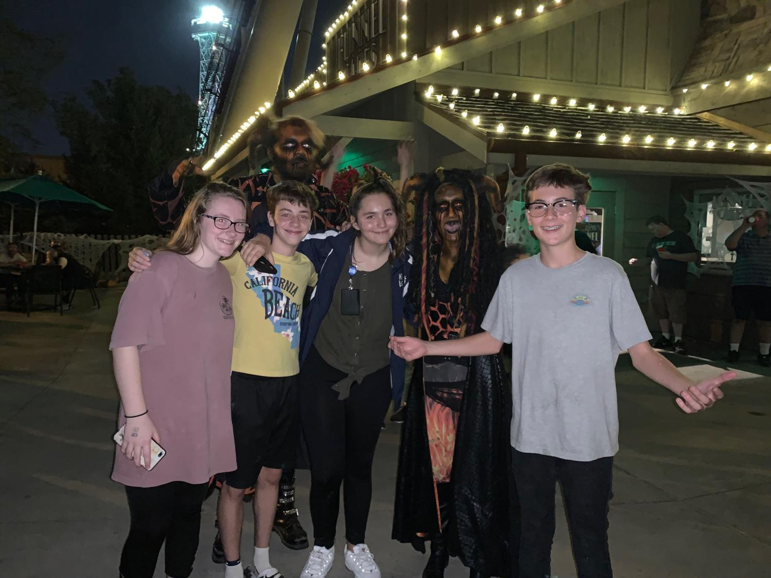 """HALLOWEEN HAUNT. From left to right, Catherine Miller, 9, Noam Rochman, 10, Leslie Nordman, 9, and Corwin McAvoy, 9, are pictured with some spooky monsters at Kings Island for Haunt. They are avid-haunted house lovers and all hang out together to enjoy the Halloween season. She loves the """"rush of excitement"""" said Nordman."""