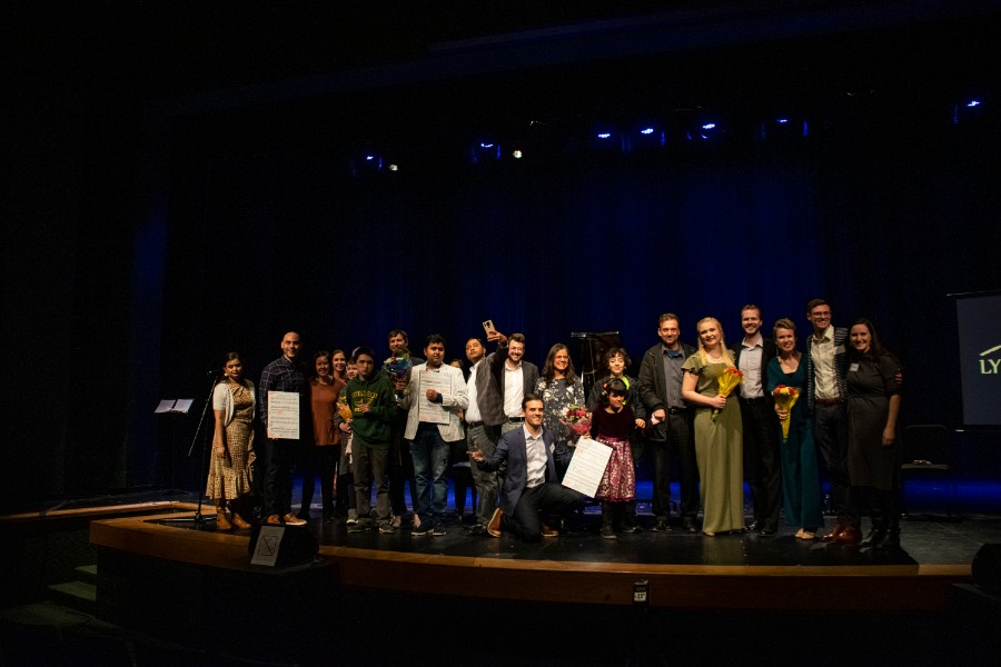 """CREATING LYNX. The Lynx Project's staff, performers, young writers and their families gather on stage for a photo after the concert. The Lynx Project set words written by young people with autism who are nonverbal to music for voice and piano, and provides these students with an outlet to share their voice.  Caitleen Kahn, executive director and co-founder, shared that she would love to see """"this music performed more widely"""" and have a """"broader impact."""" Photo courtesy of Kate Hursh."""